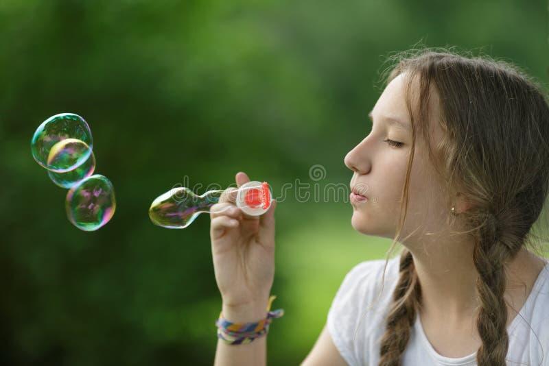 El adolescente sopla charlas del jabón en parque del te imagenes de archivo