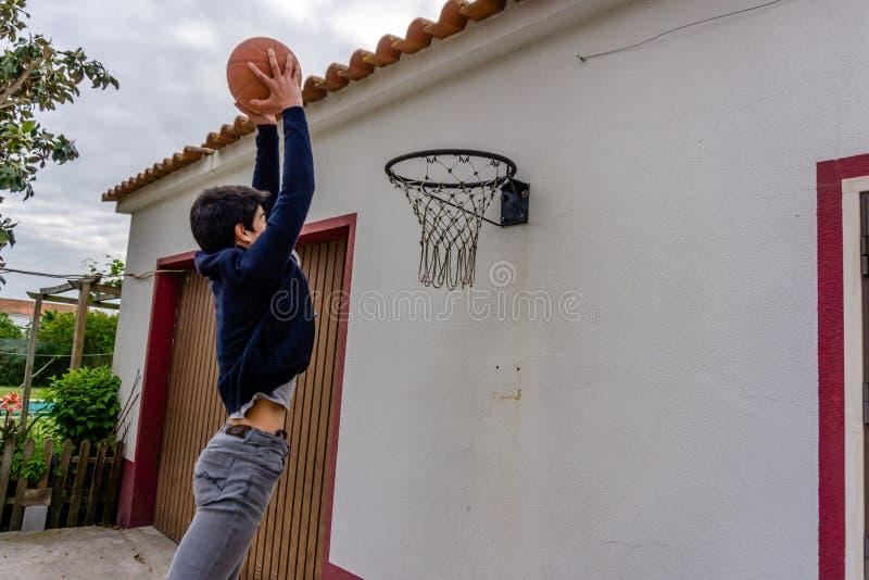 El adolescente tira el baloncesto hacia el aro montado sobre la puerta del garaje foto de archivo