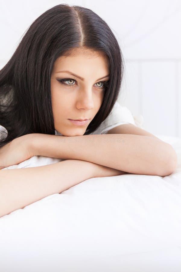 El adolescente triste refleja cuidadosamente la mentira en la cama foto de archivo libre de regalías