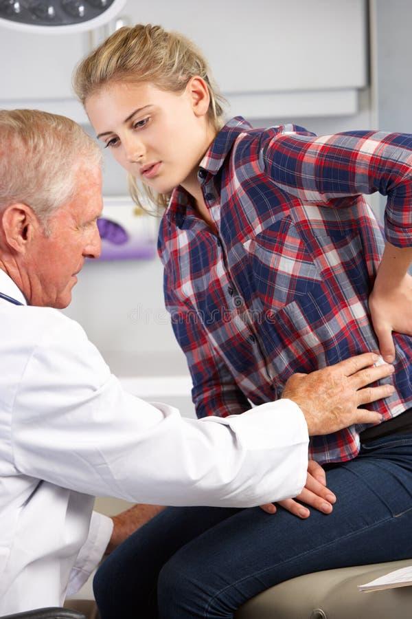 El adolescente visita el dolor de espalda de Office With del doctor foto de archivo