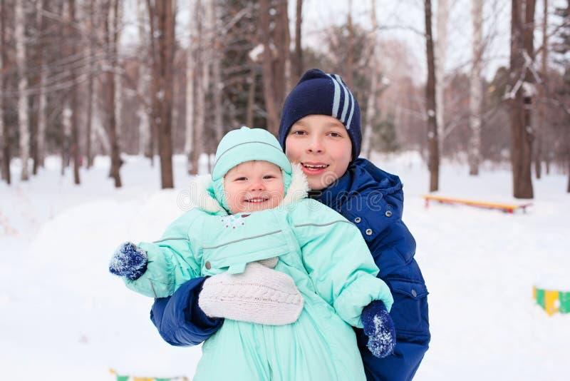 El adolescente y el bebé felices de la familia embroman en parque del invierno fotografía de archivo libre de regalías