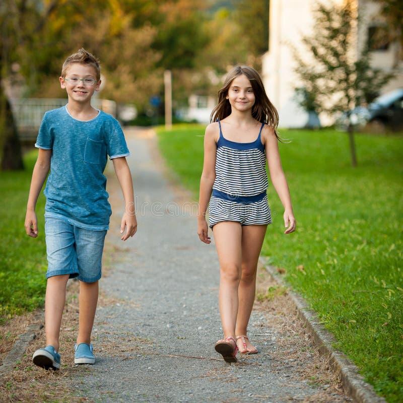 El adolescente y la muchacha jovenes caminan en parque en la ciudad foto de archivo
