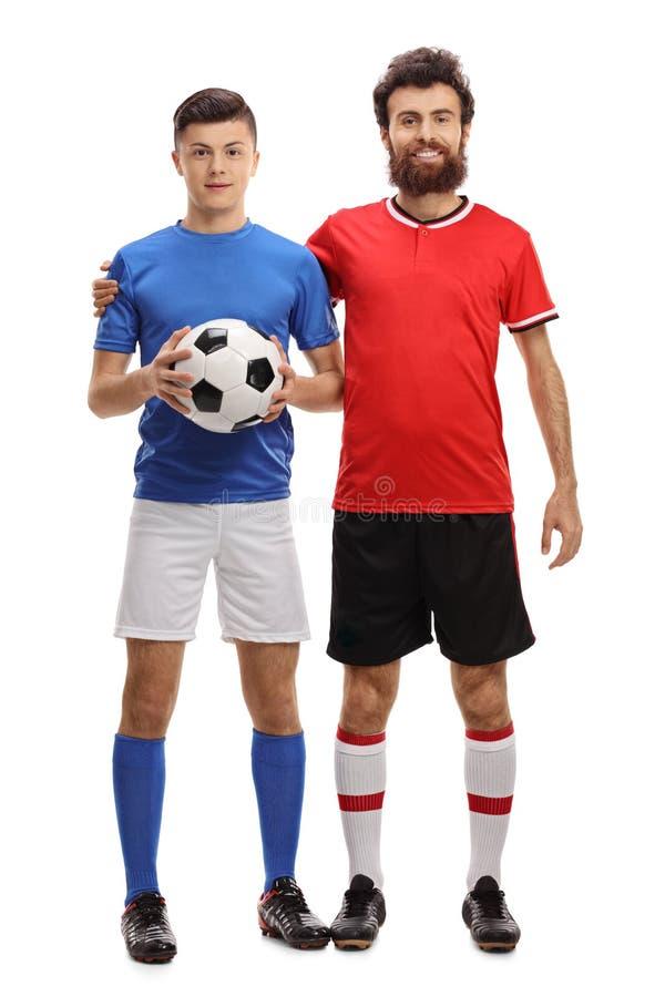 El adolescente y su padre con un fútbol se vistieron en ropa de deportes imagenes de archivo
