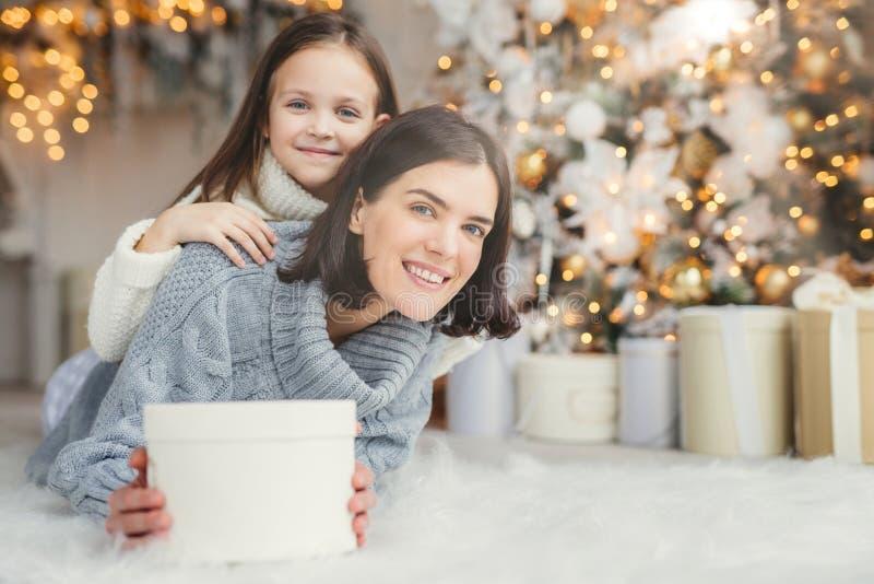 El adulto femenino sonriente de la morenita y su pequeño niño adorable hermoso en el suéter blanco que está en sala de estar, lle fotografía de archivo