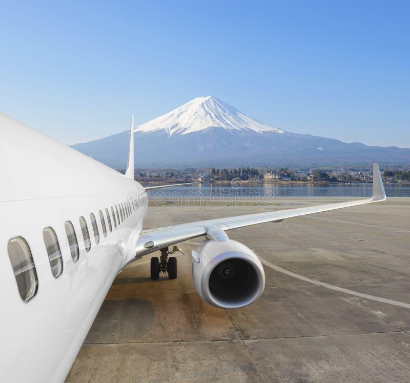 El aeroplano comercial parqueó en el aeropuerto con el Mt Fuji en fondo del invierno fotografía de archivo