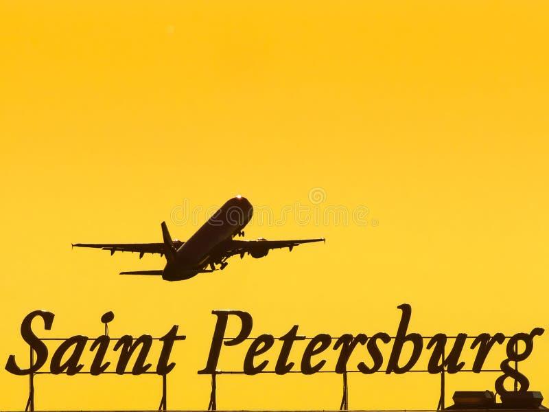 El aeroplano en despegue vuela sobre la inscripción de la ciudad de St Petersburg en la puesta del sol imagen de archivo libre de regalías