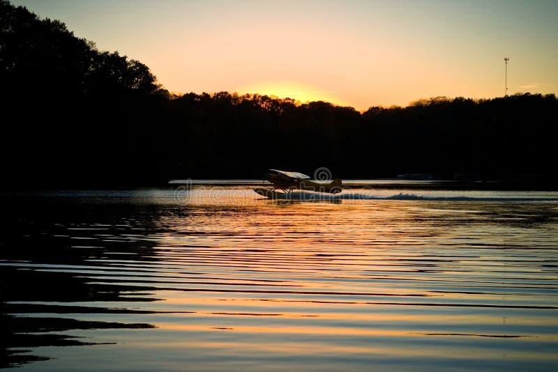 El aeroplano en el lago como el sol fija fotografía de archivo