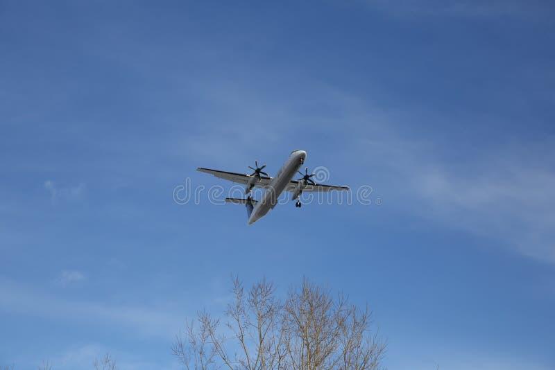 El aeroplano está volando en el cielo azul imagen de archivo