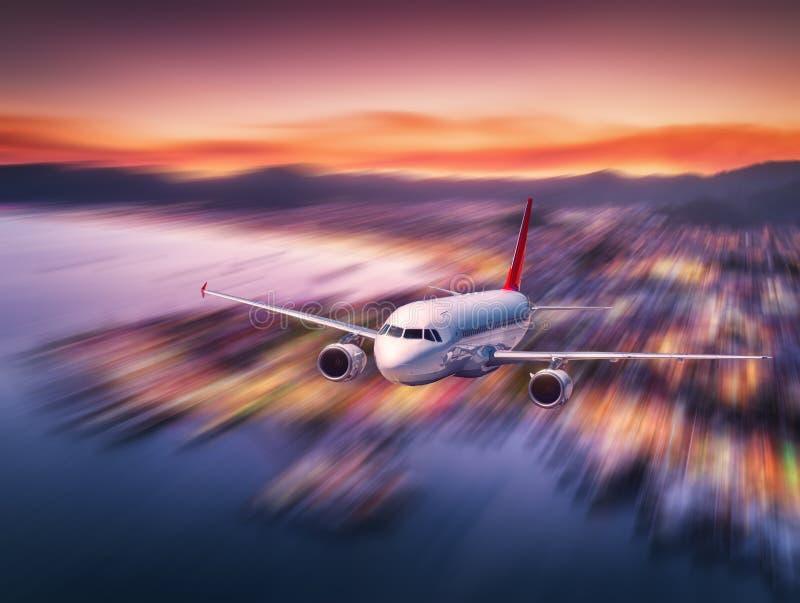 El aeroplano está volando sobre costa y ciudad de mar en la noche foto de archivo libre de regalías