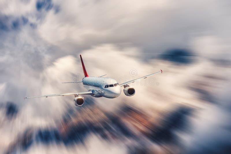 El aeroplano moderno con efecto de la falta de definición de movimiento está volando en nubes encima foto de archivo