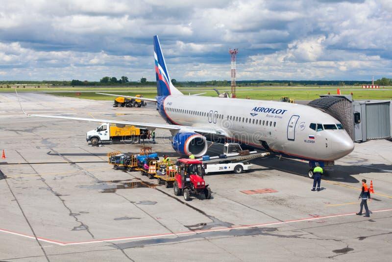El aeropuerto de Tolmachevo, servicios del servicio en tierra del aeroplano Boeing 737-800 nombró después de N Leskov, líneas aér fotos de archivo