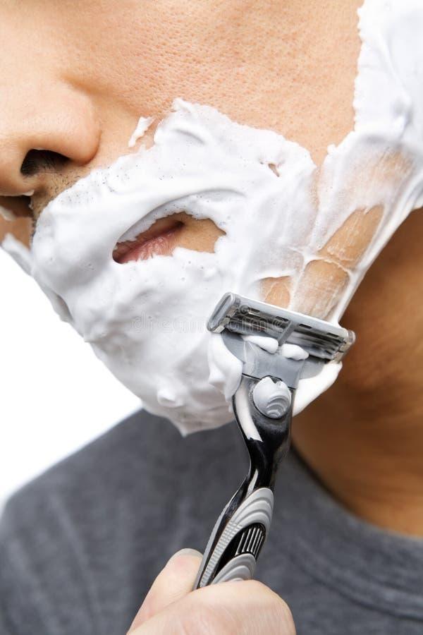 El afeitar asiático del hombre fotografía de archivo libre de regalías