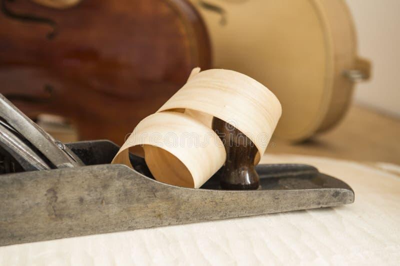 El afeitar de madera encrespado alrededor del avión de la carpintería imagen de archivo