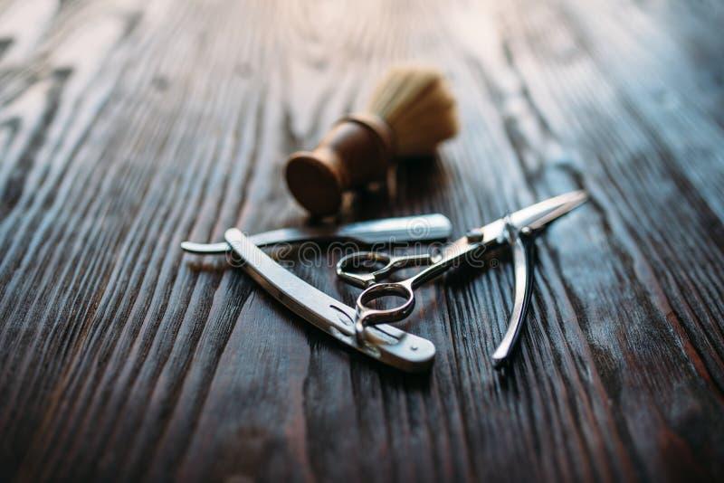 El afeitar y equipo del peluquero en fondo de madera imagen de archivo