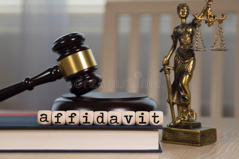 El AFFIDAVIT de la palabra integrado por de madera corta en cuadritos Mazo y estatua de madera de Themis en el fondo fotos de archivo libres de regalías