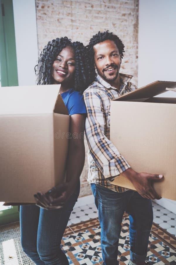 El africano negro joven sonriente junta las cajas móviles en nuevo hogar juntas y la fabricación de una vida acertada Familia ale fotos de archivo