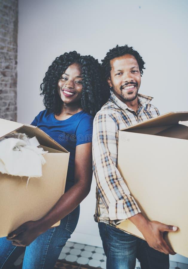 El africano negro joven sonriente junta las cajas móviles en nuevo hogar juntas y la fabricación de una vida acertada Familia ale imágenes de archivo libres de regalías