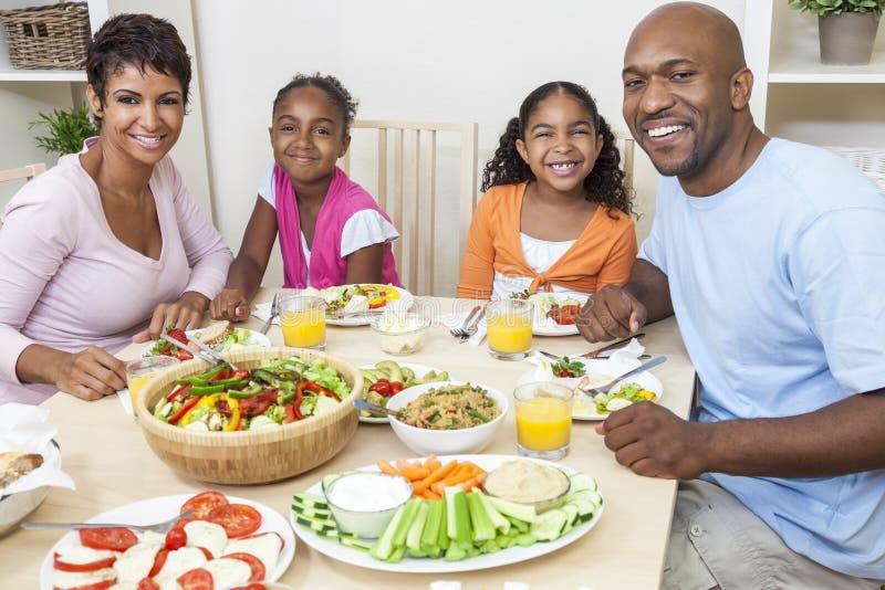 El afroamericano Parents a la familia de los niños que come en la mesa de comedor imagen de archivo