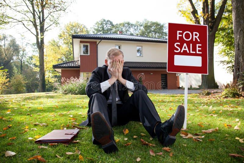 El agente de la propiedad inmobiliaria cansado se está sentando en hierba fotos de archivo libres de regalías