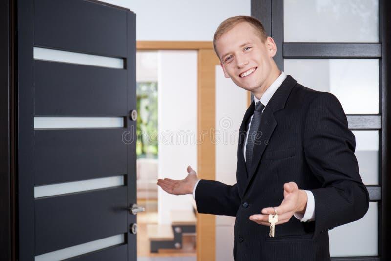 El agente de la propiedad inmobiliaria invita a clientes que vean la casa fotografía de archivo libre de regalías