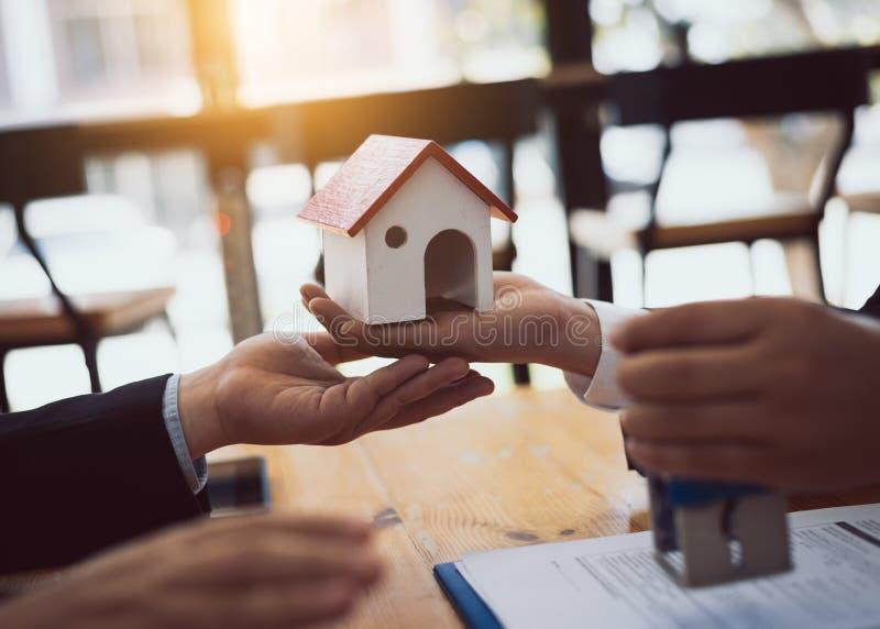El agente de la venta de las propiedades inmobiliarias de la casa revisa los documentos que se han aprobado para el préstamo del  fotos de archivo