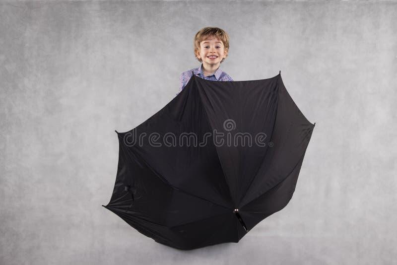 El agente de seguro joven resalta de detrás un paraguas imagenes de archivo