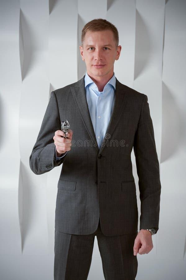 El agente del hombre de negocios sostiene el arma fotos de archivo libres de regalías