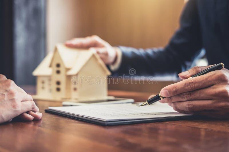 El agente del agente inmobiliario que presenta y consulta al cliente a d imágenes de archivo libres de regalías