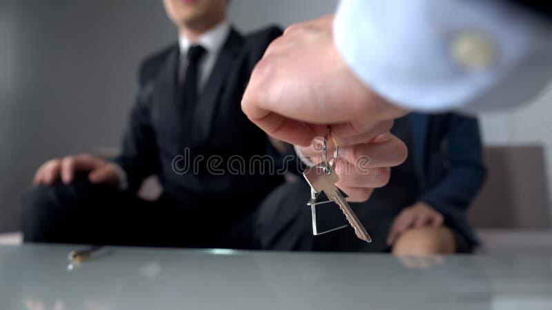 El agente inmobiliario da llave a la propiedad de compra de los pares ricos, contrato de compra imagenes de archivo