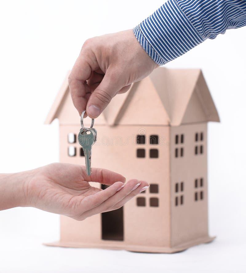 El agente inmobiliario entrega la propiedad o nuevas teclas HOME a un cliente en blanco fotografía de archivo libre de regalías