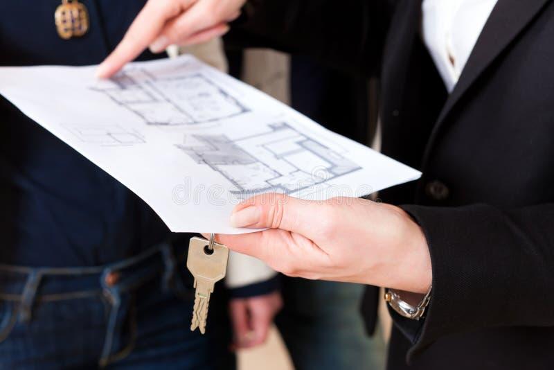El agente inmobiliario joven explica el acuerdo de arriendo de juntarse fotografía de archivo
