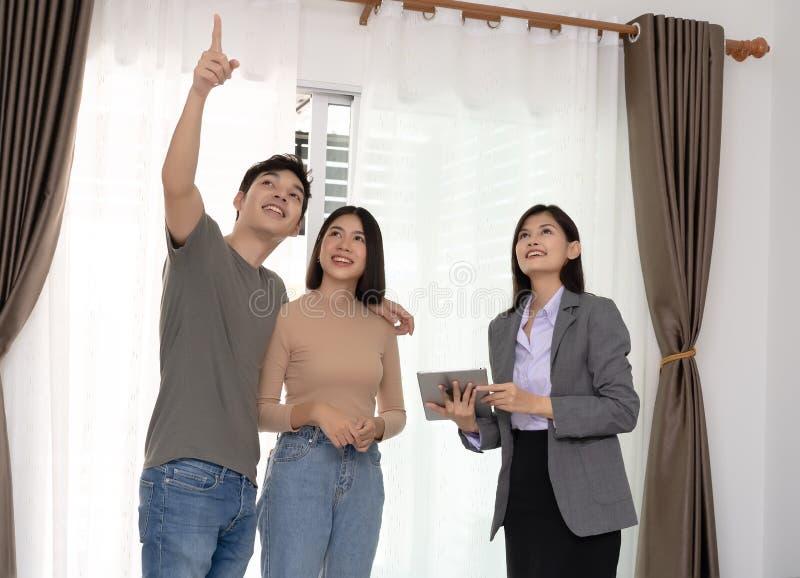 El agente inmobiliario ofrece la casa y mostrar pares asiáticos jovenes con real fotos de archivo