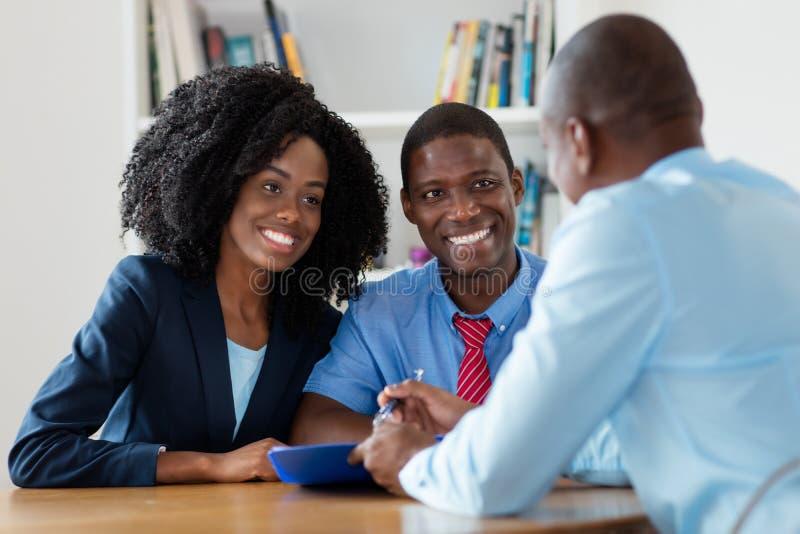 El agente inmobiliario ofrece la nueva casa para los pares afroamericanos foto de archivo libre de regalías