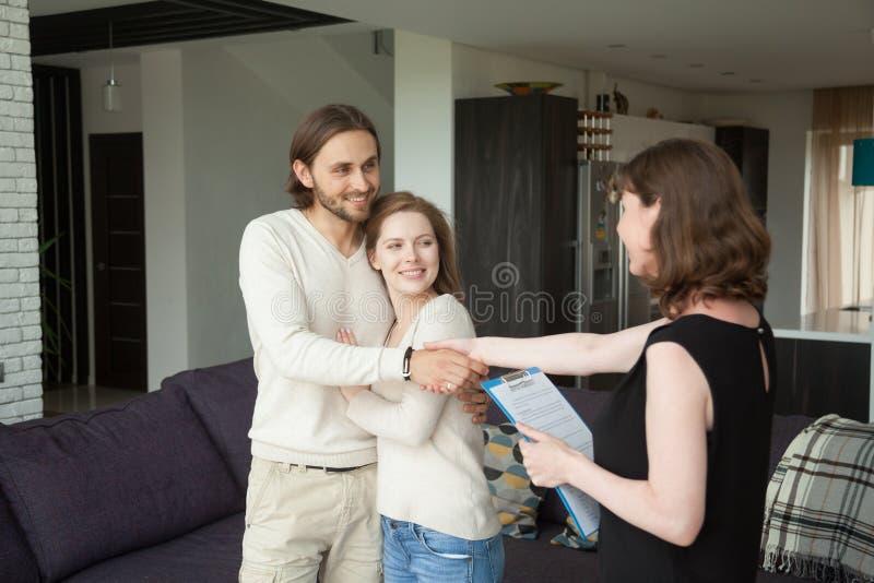 El agente inmobiliario que sacude las manos junta a clientes en casa de alquiler imagen de archivo libre de regalías