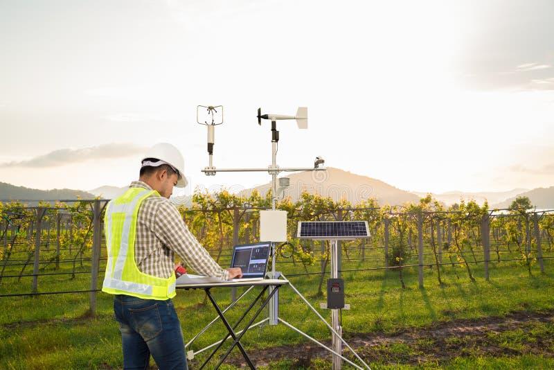 El agrónomo que usa la tableta recoge datos con el instrumento meteorológico para medir la velocidad, la temperatura y la humedad imagenes de archivo