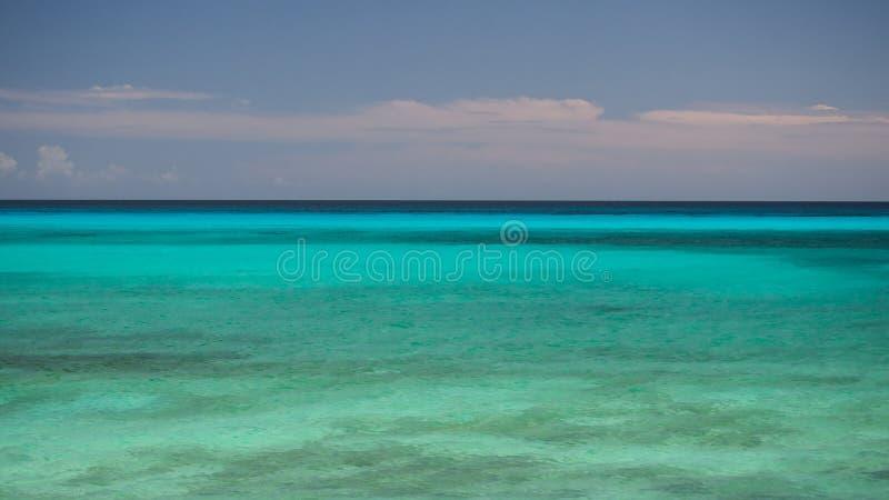 El agua apacible del océano de la turquesa al horizonte y al cielo azul foto de archivo libre de regalías