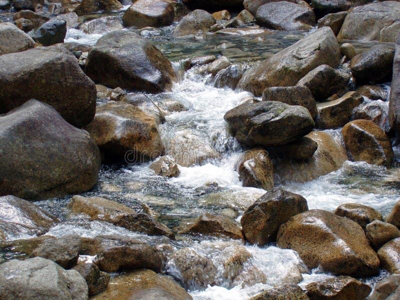 El agua cae salpicando abajo de las rocas con su opinión natural fotos de archivo