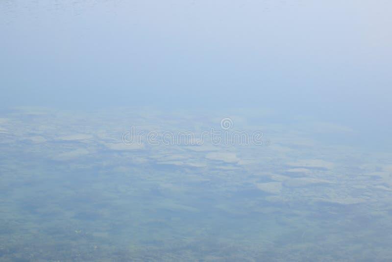 El agua clara del nuevo lago nombró Milada en mañana de la primavera en República Checa foto de archivo