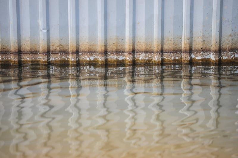 El agua en el piso con el modelo llano de la mancha en el cinc oxidado del viejo daño plat la pared fotos de archivo