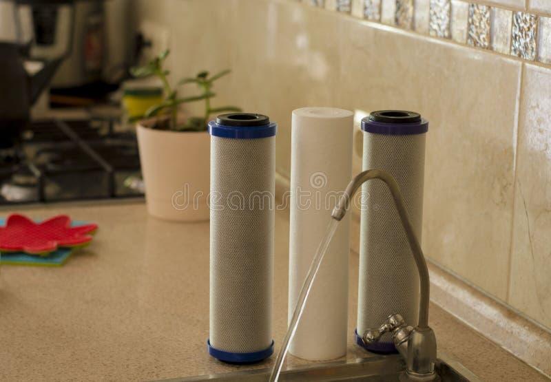 El agua filtra el agua de cocción del agua potable foto de archivo