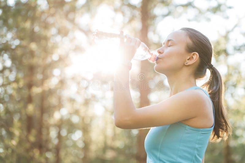 El agua potable de la mujer después de resuelve el ejercicio el la tarde de la puesta del sol imagenes de archivo