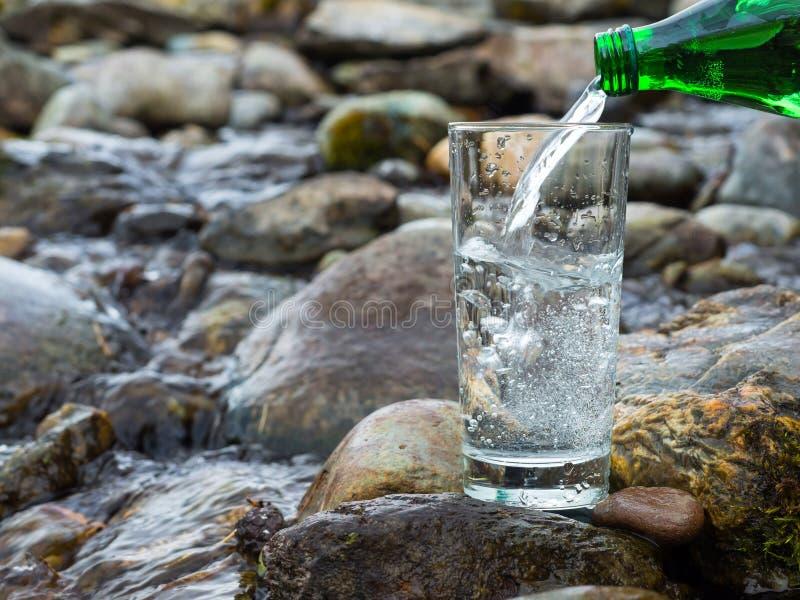 El agua potable natural se está vertiendo en el vidrio fotografía de archivo libre de regalías