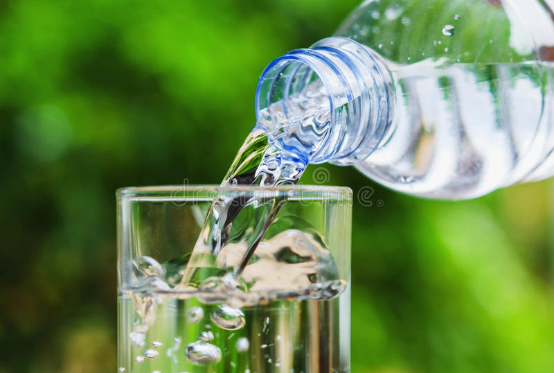 El agua potable vertió en el vidrio y la luz del sol foto de archivo