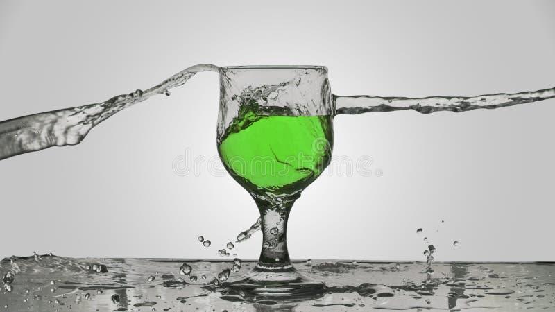 El agua salpicó en un vidrio de vino verde fotos de archivo libres de regalías