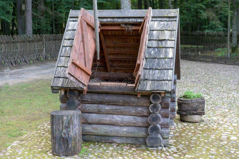 El agua vieja con la polea se cerró bien por el obturador de madera imágenes de archivo libres de regalías