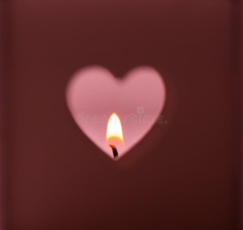 El agujero de las formas del corazón cortó en luz ardiente de la vela del fondo rojo oscuro en el contexto rosado, romántico, med fotografía de archivo