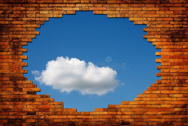 El agujero en la pared de ladrillo muestra el cielo azul fotos de archivo libres de regalías