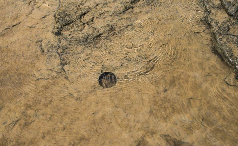 El agujero redondo se perfora adentro las rocas debajo del agua fotografía de archivo