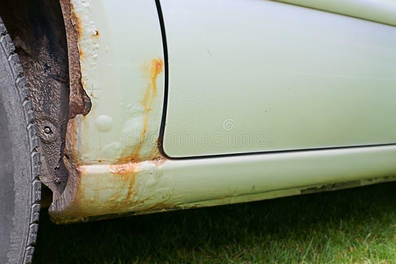 El aherrumbrar del arco del coche, del umbral y de la rueda fotografía de archivo