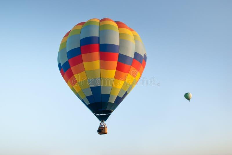 El aire caliente colorido dos hincha en fondo del cielo azul imagen de archivo